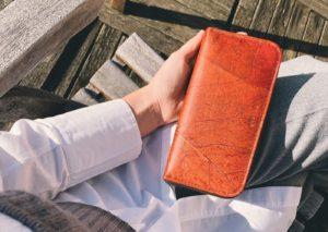 Frau mit einem braunen BELEAF Portemonnaie in der Hand