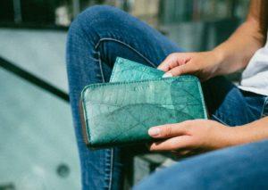 Frau mit einem türkisen BELEAF Portemonnaie in der Hand
